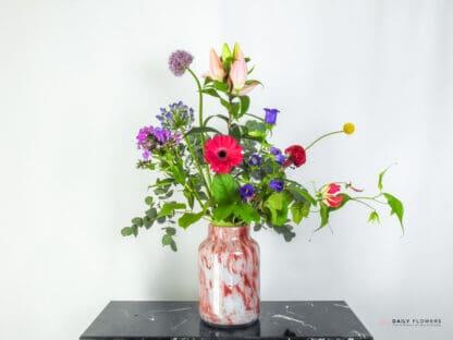 Gekleurd boeket in een roze vaas